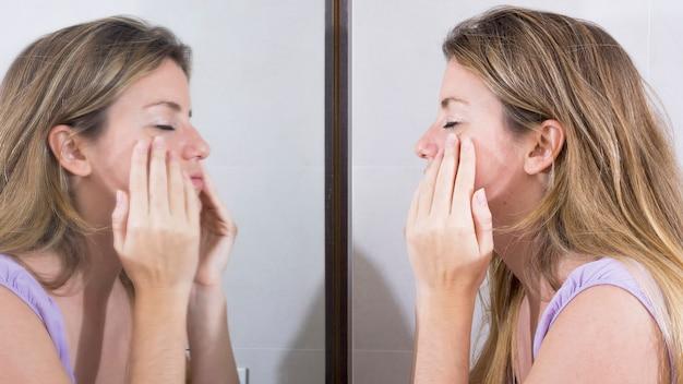 Weerspiegeling van vrouw in de spiegel die haar gezicht wast