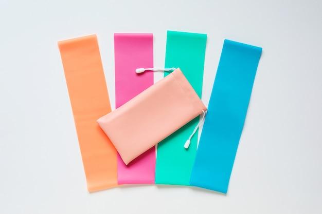 Weerstandsbanden en opbergzakje op witte achtergrond kleurrijke fitness elastische banden sportartikelen