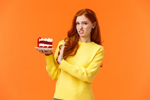 Weerzinwekkende en ontevreden, kieskeurige roodharige vrouw zorgt voor lichaamsvorm, eet geen snoep