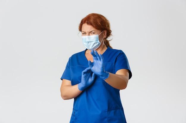 Weerzinwekkende en onwillige vrouwelijke arts in gezichtsmasker en handschoenen die iets vermijden
