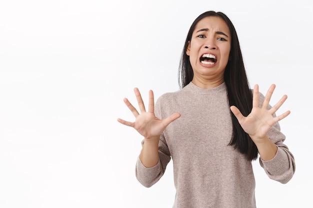 Weerzinwekkende en verontwaardigde, kieskeurige jonge oost-aziatische vrouw drukt walging en teleurstelling uit, voelt zich bang dat iemand haar heeft aangevallen, hand opsteken om te stoppen, smeken om genade, ineenkrimpen en geschokt grimassen