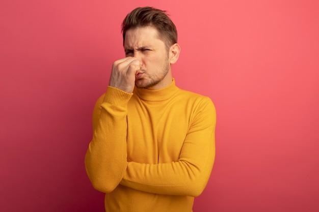 Weerzinwekkende jonge blonde knappe man die neus vasthoudt en naar de zijkant kijkt en een stankgebaar doet geïsoleerd op een roze muur met kopieerruimte