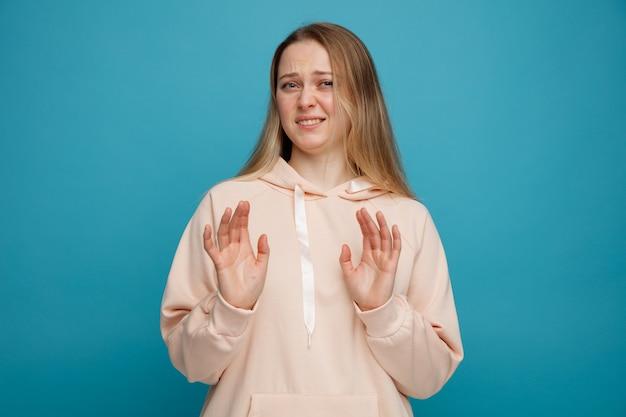 Weerzinwekkende jonge blonde vrouw die weigeringsgebaar doet
