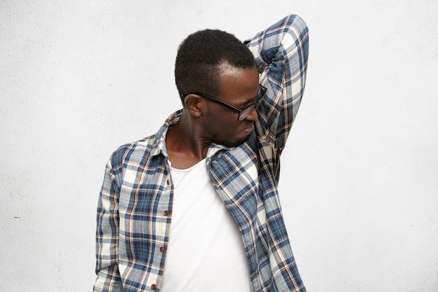 Weerzinwekkende jonge man met geruit hemd en bril die nat zwetende oksel ruiken na een stressvolle ontmoeting, misselijk voelende, knellende lippen. een zwarte man kan geen slechte geur verdragen. hyperhidrose en hygiëne