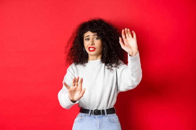Weerzinwekkende jonge vrouw die smeekt om te stoppen, verdedigende handen opheft, nee zegt, staande op rode achtergrond. kopieer ruimte
