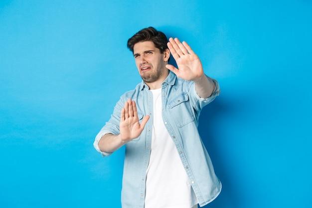 Weerzinwekkende man die nee zegt, weigert en wegkijkt van iets vreselijks, ineenkrimpt terwijl hij tegen een blauwe achtergrond staat