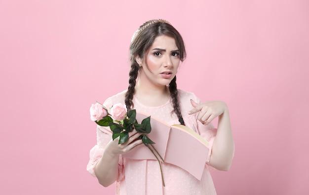 Weerzinwekkende vrouw met rozen en wijzend op boek