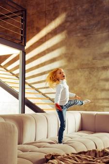 Wees actief. vrolijk meisje dat op het rechterbeen staat en haar evenwicht bewaart