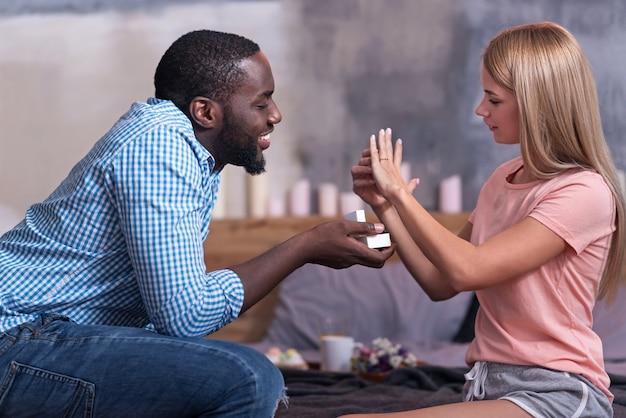 Wees de mijne. afrikaanse gelukkig jongeman bruiloft cadeau geven aan zijn vriendin en voorstel doen terwijl ze probeert op de verlovingsring