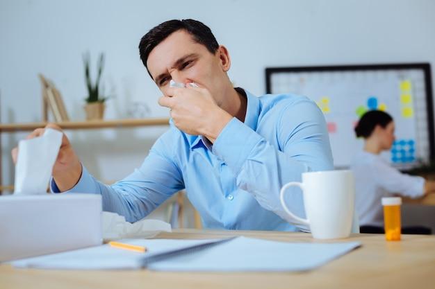 Wees gezond. attente mannelijke persoon die zijn neus bedekt en ellebogen op tafel legt terwijl hij aan het werk is