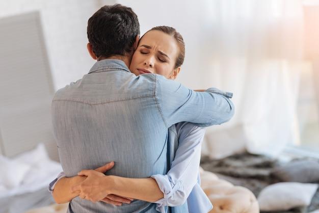 Wees hier. vermoeide jonge ontslagen vrouw voelt zich beter terwijl ze staat en haar vriendelijke, betrouwbare ondersteunende echtgenoot knuffelt