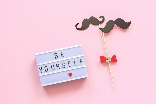 Wees jezelf lightbox-tekst, paar papier snor rekwisieten op roze achtergrond. homoseksualiteit homo liefde