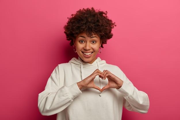 Wees mijn valentijn. aangenaam uitziende krullende vrouw drukt liefde uit, maakt hartgebaar, heeft romantische gevoelens