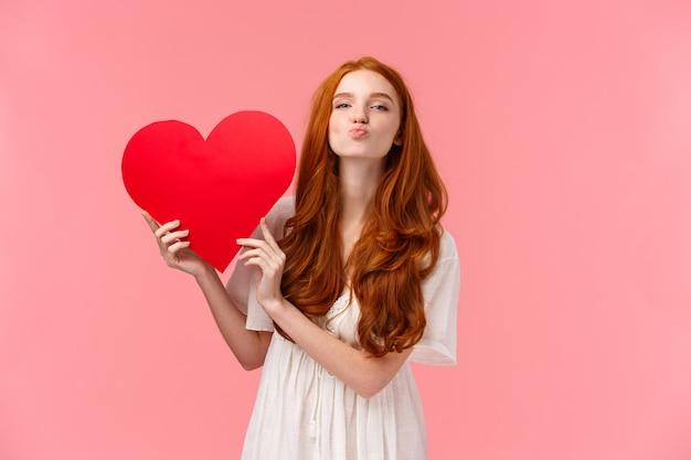 Wees mijn valentijn. mooie en sensuele, tedere roodharige vriendin die liefde en zorg uitdrukt, gefeliciteerd met valentijnsdag, met groot rood hart, vouwen lippen sturen luchtkus naar, roze muur