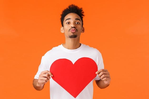 Wees mijn valentijn. romantische schattige afro-amerikaanse man op zoek naar ware liefde, lippen vouwen en kus geven, groot schattig hartkarton vasthouden, staande oranje muurshow affectie