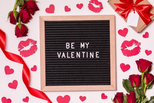 Wees mijn valentijn - tekst op het bord met valentijnsdag achtergrond - rode rozen, kussen en harten.