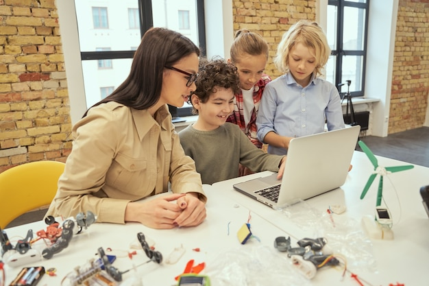 Wees nieuwsgierig lachende kinderen kijken naar wetenschappelijke robotica video zittend aan de tafel in een klaslokaal
