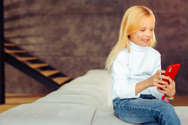 Wees positief. blij blond kind dat in de woonkamer zit en rust heeft