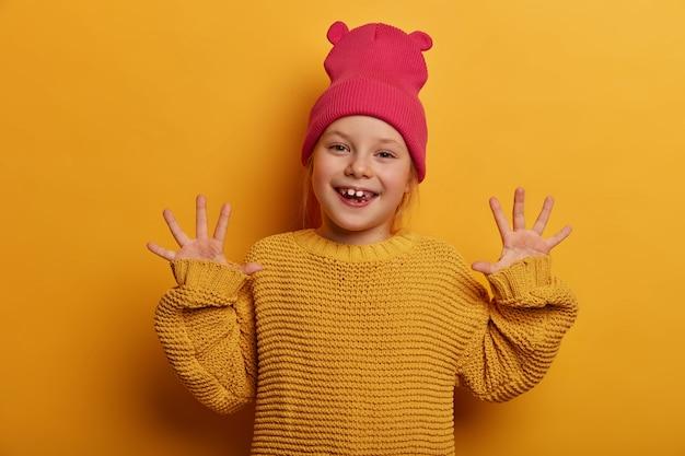 Wees positief en blijf glimlachen. blij schattig europees kind steekt zijn handen op en toont zijn handpalmen, drukt goede emoties uit, speelt met iemand, gekleed in gebreide trui, geïsoleerd op gele muur