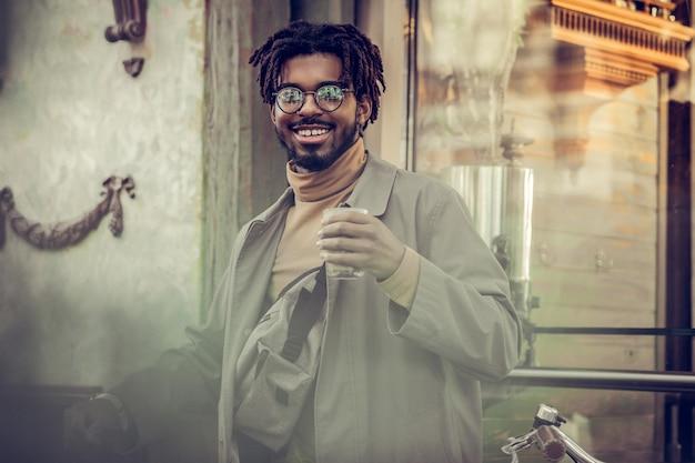 Wees positief. opgetogen freelancer die een glimlach op zijn gezicht houdt terwijl hij voor de camera poseert
