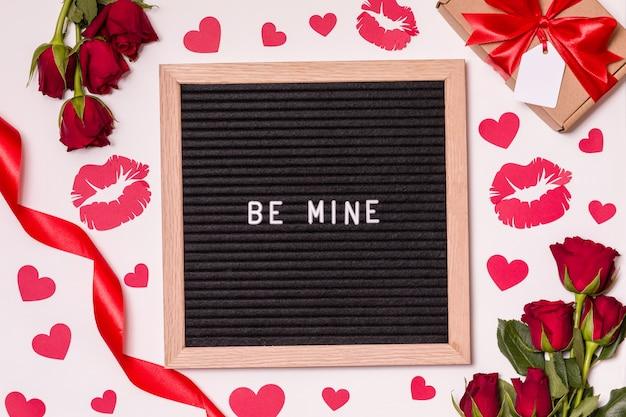 Wees van mij - tekst op brief bord met valentijnsdag achtergrond - rode rozen, kussen en harten.