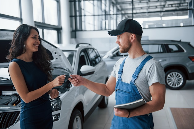 Wees voorzichtig de volgende keer. vrouw in de autosalon met werknemer in blauw uniform die haar gerepareerde auto terugneemt