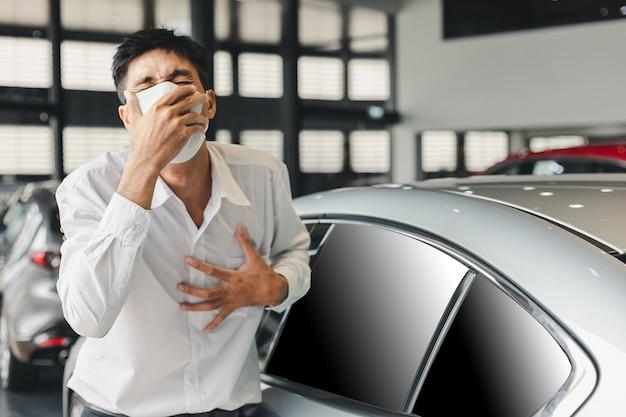 Wees voorzichtig voordat u gaat rijden dit is een werkende man geïnfecteerd virus covid-19 of corona symptomen vertonen tijdens het rijden moet worden beschermd in een showroomdealer, auto, auto station