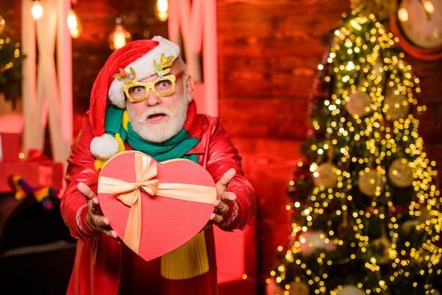 Wees vrolijk. stapel geschenken onder de kerstboom. cadeautjes van de kerstman met liefde. gelukkig man met baard. kerst decoratie. gelukkig nieuwjaar thuis. wintervakantie winkelen. feest feest.