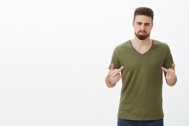 Weet je wat, fuck you. portret van pissig, boos en beledigd knappe bebaarde man die ruzie heeft met beste vriend, verraden wordt pruilend van woede met middelvingers, fronsend woedend