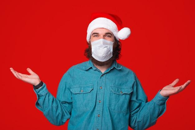 Weet niet wat te doen, bebaarde man met medicinale masker en kerstman hoed, pandemie tijd