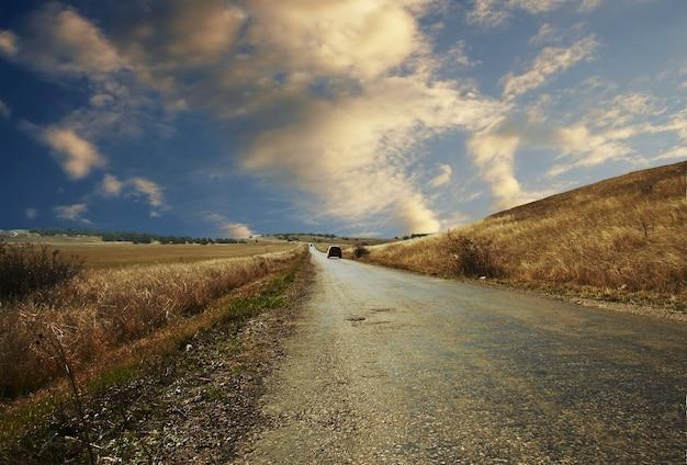 Weg-, auto- en zonsondergangwolken in de berg van de krim