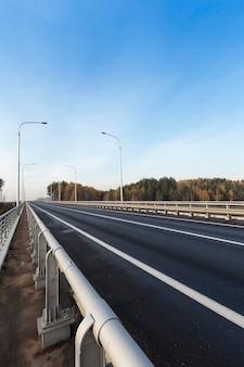 Weg die over de brug over de rivier gaat. de foto is in de herfst van dichtbij genomen. men kan de blauwe lucht en de pilaren zien, die 's nachts verlicht zijn. Premium Foto