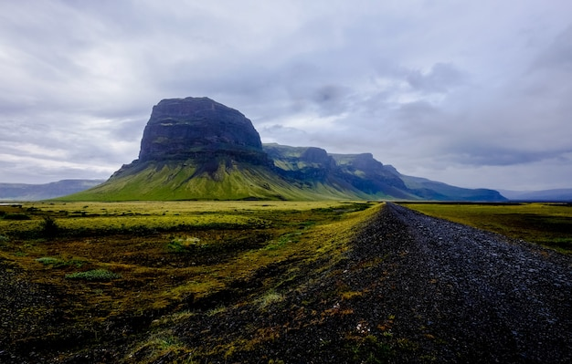 Weg in het midden van grasvelden en bergen in de verte onder een bewolkte hemel