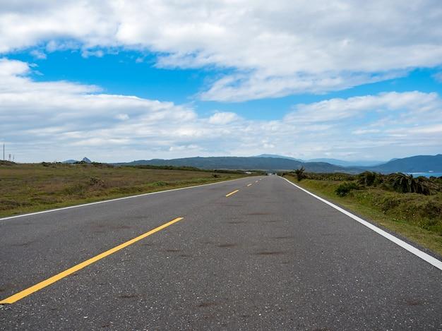 Weg in kenting met aan de horizon bergen en kust.