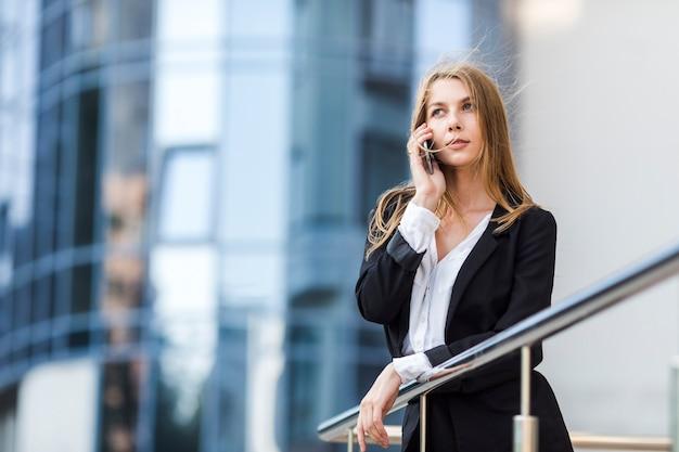 Weg kijkend vrouw die op de telefoon spreekt
