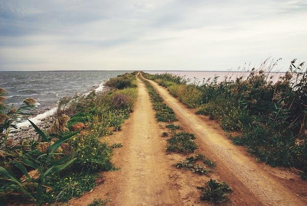 Weg naar nergens - lege zandspitsweg door zoutmeer