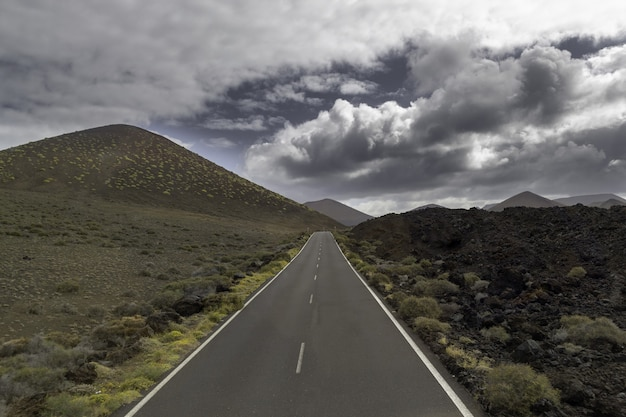 Weg omgeven door heuvels onder een bewolkte hemel in het timanfaya national park in spanje