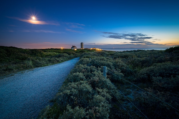 Weg omgeven door struiken en groen die leidt naar een nederzetting en een zee bij zonsondergang