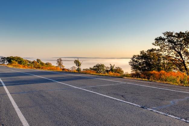 Weg op het platteland met mooie natuur in de herfst seizoen en vallei bedekt met mist