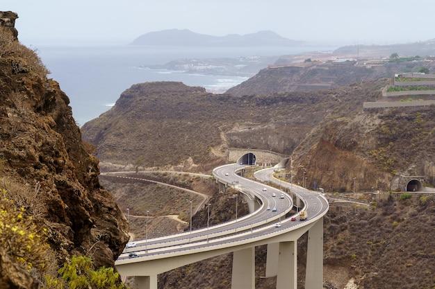 Weg over een enorme brug die aan de zee grenst aan de bergen op het eiland gran canaria. spanje, europa,