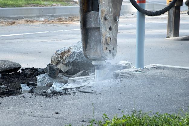 Weg reparatie. verwijderen van een oude laag asfalt met een hydraulische hamer. bestrating reconstructie.