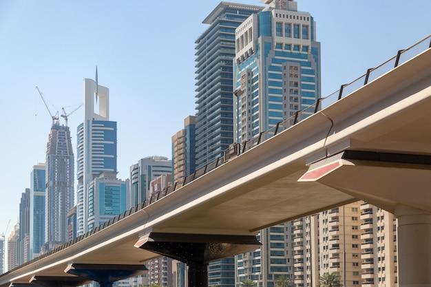 Weg tegen de blauwe lucht en hoge woon- en kantoorgebouwen