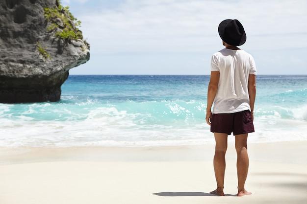 Weg van toeristische paden. op blote voeten jonge kaukasische avonturier die op zandige kust voor stenen eiland in turkooise oceaan staat die hij uiteindelijk tijdens zijn lange reis langs kustlijn vond
