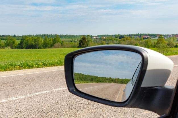 Weg weerspiegeld in zijspiegel van auto op een zonnige dag. reis concept