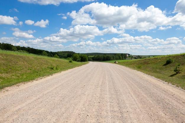 Weg zonder asfalt, door het veld met maïs en bos. lente landschap met blauwe lucht en wolken op de achtergrond. platteland