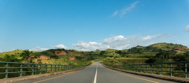 Wegbrug omgeven door heuvels en groen over de rivier de keve in angola