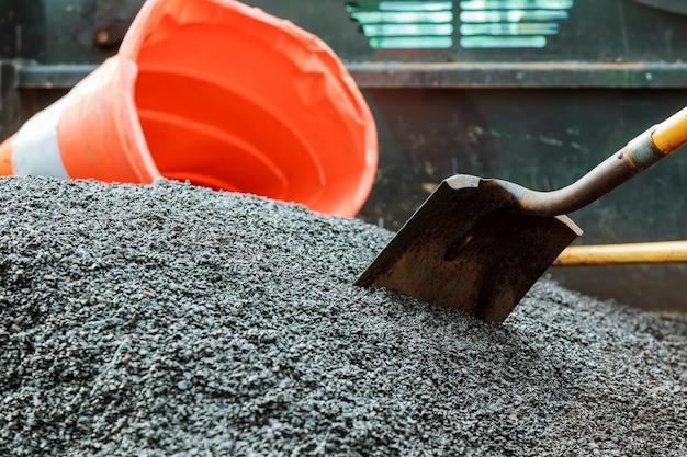 Wegenbouw. nieuw asfaltbeton, betonnen stoeprand en oranje veiligheid