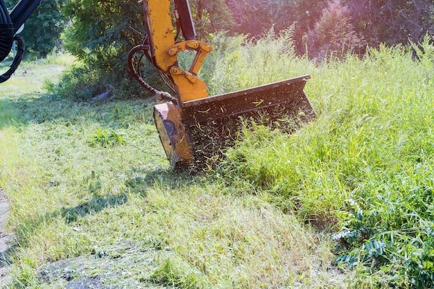Wegendiensten houden zich bezig met een tractor met een mechanische maaier die gras maait aan de kant van de asfaltweg, landschapsarchitectuur rond wegen