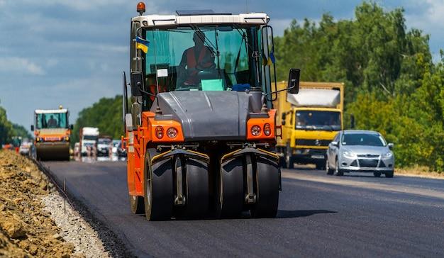 Wegenreparatie, compactor legt asfalt. zware speciale machines. asfaltafwerker in bedrijf. zijaanzicht. detailopname.