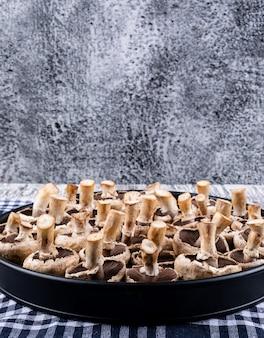 Weggeknipte paddestoelen in een kookpot op een picknickdoek en grijze houten tafel